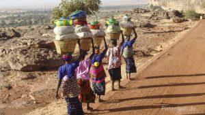 Frauen transportieren geschickt ihre Waren zum Markt
