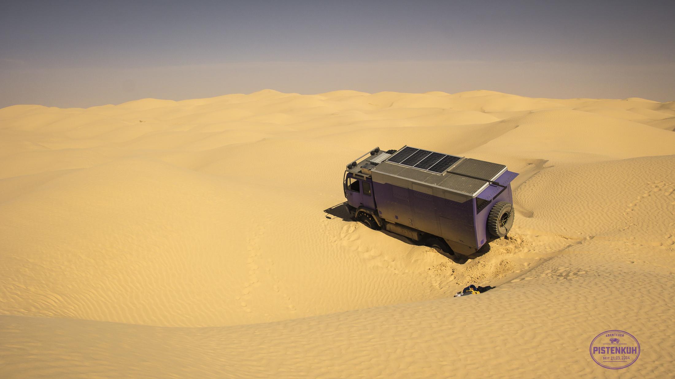 Pistenmobil steht schräg im Sand